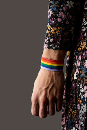 closeup of a young caucasian woman with a rainbow-patterned ribbon tied to her wrist, against a gray background
