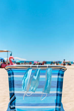 some surgical masks hanging on a blue deck chair on the beach, with the sea in the background Stock Photo