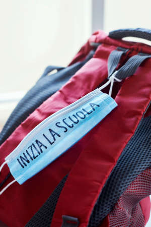 closeup of a red and gray bookbag and a blue surgical mask with the text back to school written in italian, depicting the need to prevent the infection at school in the covid-19 pandemic situation