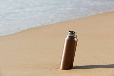 closeup of an aluminum reusable water bottle on the seashore of a lonely beach Stock fotó
