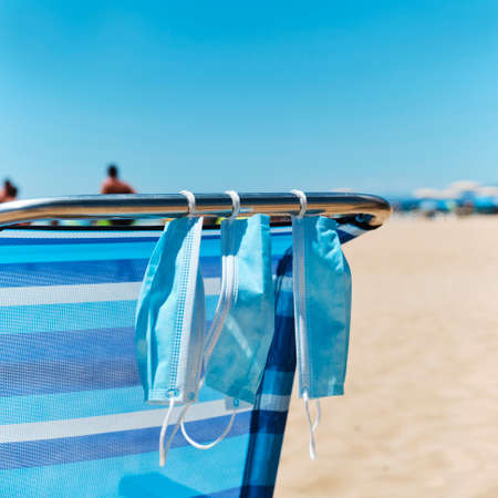 closeup of some blue surgical masks hanging on a blue deck chair on the beach Banco de Imagens