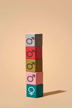 a pile of some building blocks with male gender symbols and a building block with a female gender symbol on the bottom of the stack, on a light brown background with some blank space on top