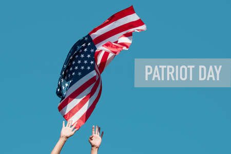closeup of a young caucasian man launching a flag of the United States to the blue sky, or about to catch it from the sky, and the text patriot day
