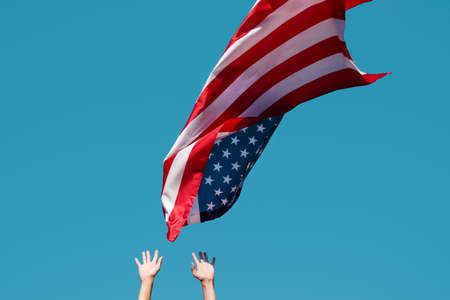 closeup of a young caucasian man launching a flag of the United States to the blue sky, or about to catch it as it flights in the air