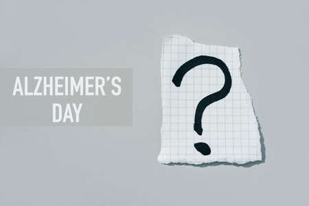 a question mark in a piece of paper and the text Alzheimers day on a gray background