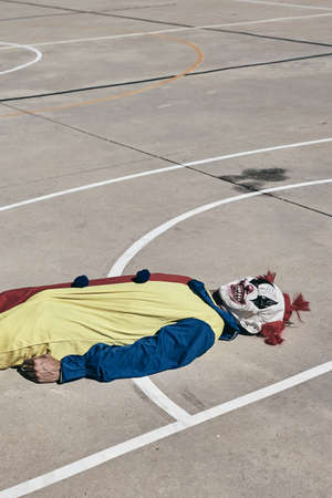 a scary clown, wearing a yellow, red and blue costume, lying face up on an outdoor basketball court