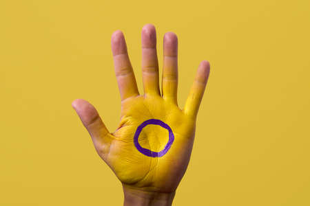 closeup of the intersex flag painted in the palm of the hand of a young person, against a yellow background with some blank space around it