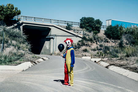 a scary clown wearing a yellow, red and blue costume, holding a black balloon in one hand and a big knife in the other hand, standing in the middle of a secondary road, at the entrance of a tunnel