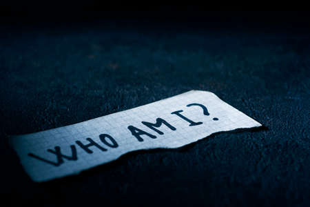 a piece of paper with the question who am I written in it, on a black textured surface Imagens
