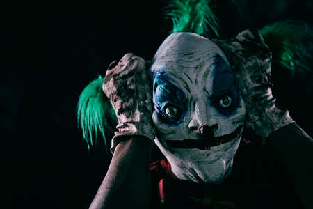 closeup of a disturbing evil clown, wearing a dirty red costume pulling his green hair with his hands wearing dirty and bloody gloves, in a black background Reklamní fotografie