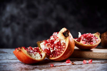 some pieces of an open pomegranate fruit on a rustic wooden table, against a dark gray background with some blank space on top