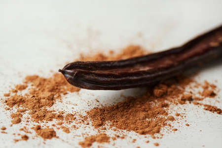 closeup of a  ripe carob pod and some carob powder on a white table