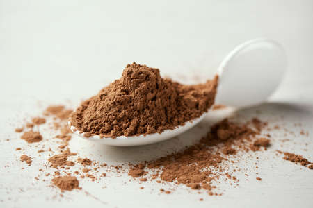 closeup of a pile of carob powder on a white ceramic spoon, placed on a white table 版權商用圖片