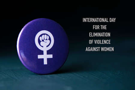 the text international day for the elimination of violence against women and the women power symbol, a raised fist in a female gender symbol, in a violet pin button Foto de archivo