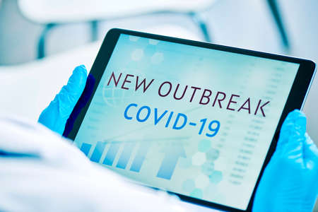 closeup of a doctor man, wearing blue surgical gloves, having a digital tablet in his hands with the text covid-19 new outbreak in its screen