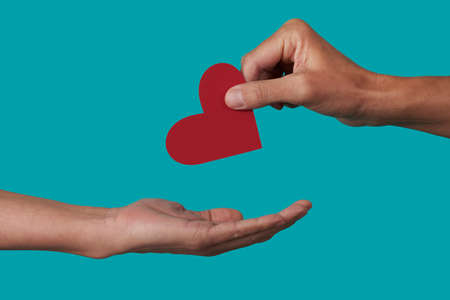a person giving a red heart to another person on a blue background Imagens