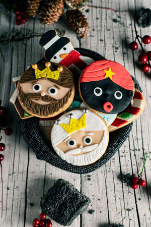 some christmas cookies, with different shapes, such as the three wise men, a snowman or a candy cane, in a gray knitted bag placed on a white rustic wooden table next to some pieces of candy coal