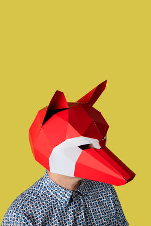 portrait of a caucasian man wearing a red and white fox mask, on a yellow background with some blank space on top