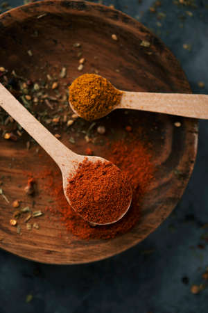 high angle view of two wooden spoons full of red curry powder and regular curry powder, on a wooden plate, placed on a dark stone surface