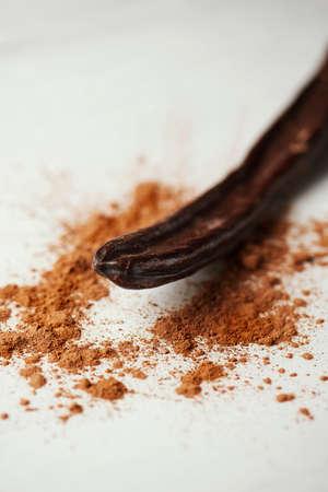 closeup of a ripe carob pod and some carob powder sprinkled on a white table 版權商用圖片
