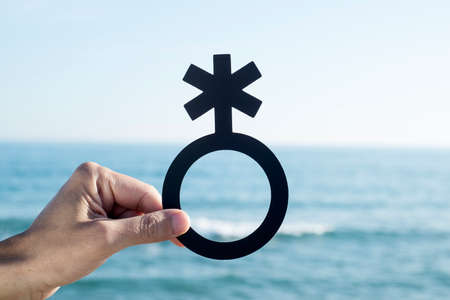 closeup of a young caucasian person holding a non-binary gender symbol in front of the ocean Stock Photo