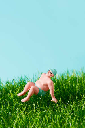 closeup of a miniature man in swimsuit relaxing sitting on the grass, against a blue background with some blank space on top Foto de archivo