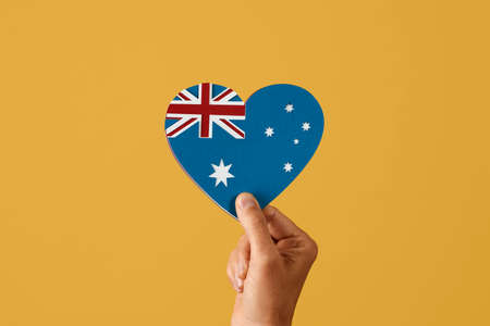 closeup of a man holding in his hand an australian flag in the shape of a heart, made with cutouts of paper of different colors, on a yellow background with some blank space around