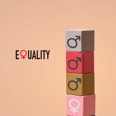 the word equality and a pile of building blocks of different colors with male gender symbols painted on them and a building block with a female gender symbol on the basis, on a brown background