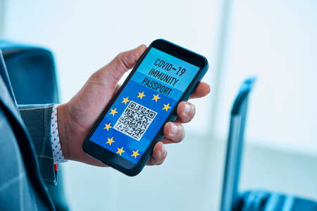 closeup of a young caucasian businessman, in a gray suit, having a simulated electronic european covid-19 immunity passport in the screen of his smartphone, sitting in the waiting hall of an airport