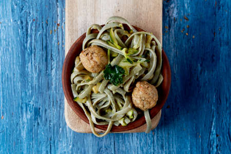 high angle view of an earthenware plate with some spelt tagliatelle with vegan meatballs, kale and zucchini, on a rustic blue wooden table