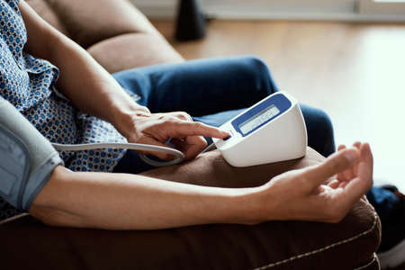 a caucasian man measures his blood pressure with an electronic sphygmomanometer, sitting at a brown sofa