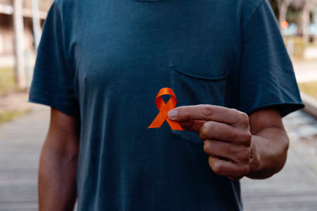 closeup of a young caucasian man outdoors, in a gray t-shirt, with an orange ribbon in his hand, in support of people affected by multiple sclerosis Foto de archivo