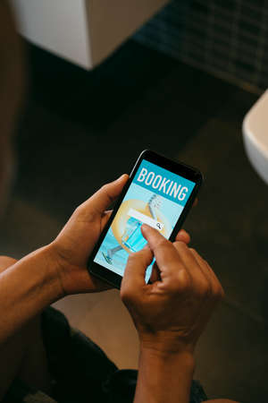 closeup of a young caucasian man, sitting in the toilet, booking his vacation online with his smartphone, with a simulated search engine in its screen