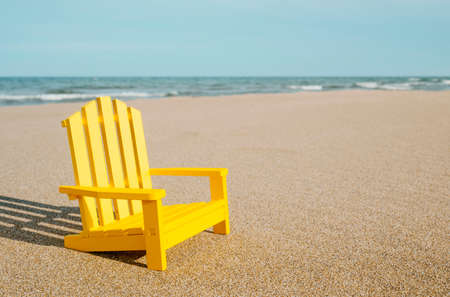 closeup of a yellow miniature chair on the sand of a lonely beach, with the sea in the background