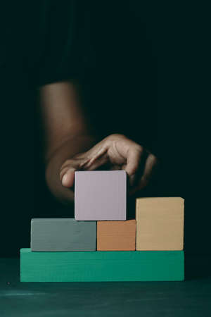 closeup of a caucasian man building a structure with some wooden toy blocks of different colors, on a dark gray surface