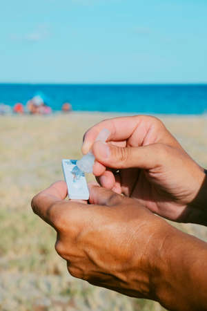closeup of a young caucasian man on the beach placing his own sample into the  antigen diagnostic test device
