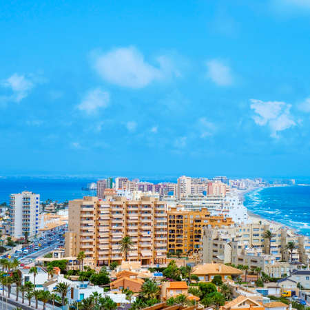 a panoramic view over La Manga del Mar Menor, in Murcia, Spain, with the Mar Menor lagoon on the left and the Mediterranean sea on the right, in a square format