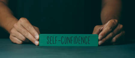 a caucasian man shows a green building block with the text self-confidence written in it, on a dark gray surface, in a panoramic format to use as web banner or header