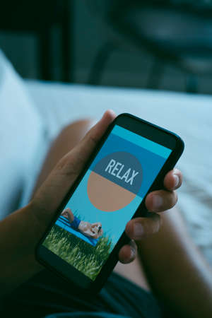 closeup of a young caucasian man resting sitting on bed while is looking at his smartphone, that reads relax in its screen Banque d'images