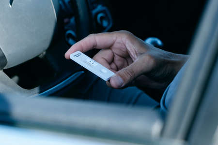 closeup of a young man, in a casual wear, looking to an antigen diagnostic test device, waiting for the results, while is sitting in the driver seat of his car