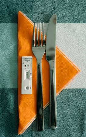 high angle view of an antigen diagnostic test device with a negative result on an orange tissue napkin, on a table set for lunch, next to a fork and a knife Banque d'images