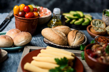 closeup of some different ingredients on a table to prepare vegan sandwiches or appetizers, such as different bread buns, cooked baby corns, cherry tomatoes, avocado or olive oil