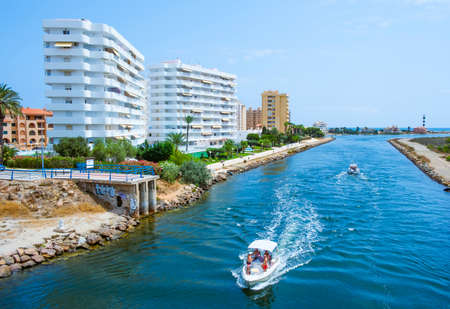 LA MANGA, SPAIN - JULY 29, 2021: View of the Gola del Puerto canal in La Manga del Mar Menor, Murcia, Spain, that connects the lagoon and the Mediterranean sea, and the Estacio lighthouse on the right