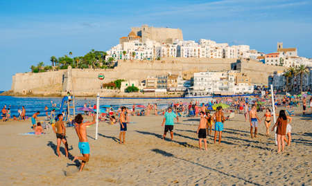 PENISCOLA, SPAIN - AUGUST 2, 2021: People enjoying on the beach in Peniscola, in Valencia, highlighting its fortified walls on the background. It is an important summer tourist destination in Spain Éditoriale