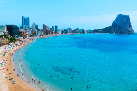 CALPE, SPAIN - AUGUST 2, 2021: A panoramic view over the main beach of Calpe, in the Valencian Community, highlighting its characteristic apartment towers and the Penon de Ifac promontory on the right