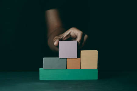 a caucasian man builds a structure with some wooden toy blocks of different colors, on a dark gray surface