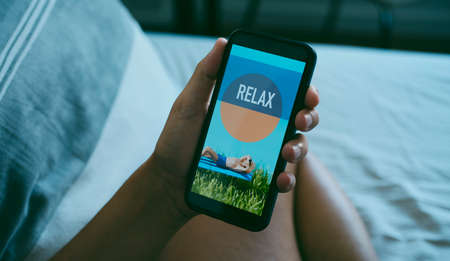 a young caucasian man is sitting comfortably on bed while is looking at his smartphone, that reads relax in its screen, in a panoramic format to use as web banner or header
