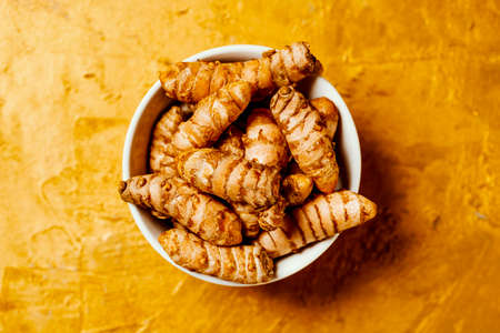 high angle view of some turmeric roots, curcuma longa species, in a ceramic bowl placed on a golden textured surface
