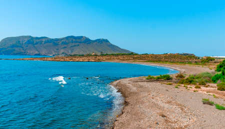 a panoramic view over the lonely El Rafal beach, in Aguilas, in the Costa Calida coast, Region of Murcia, Spain, with the mountain of the Cope cape in the background