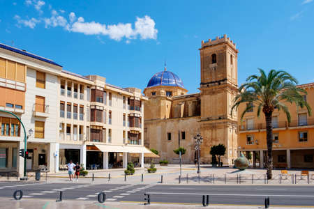 Elche, Spain - July 26, 2021: A view over the Palau Square in Elche, Spain, highlighting the dome and the belltower of the Basilica of Santa Maria church, dedicated to the Virgin Mary Éditoriale